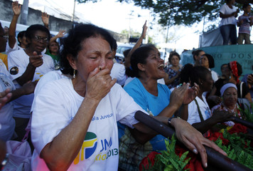 A faithful reacts during the visit of the World Youth Day symbols at the Vidigal slum in Rio de Janeiro