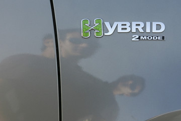 Visitors are reflected on a Hybrid model at a car showroom in Amman