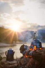 Lagerfeuer mit Wasserkessel am Fluss