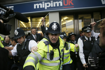 Police officers scuffle with demonstrators outside the MIPIM property fair at Olympia in London