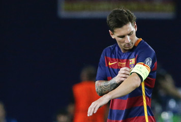 Barcelona's Lionel Messi puts on the captain's armband during the UEFA Super Cup soccer match against Sevilla at Boris Paichadze Dinamo Arena in Tbilisi