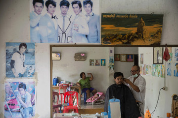 A barber is reflected in a mirror as he cuts a customer's hair at his shop in Ban Nam Khem