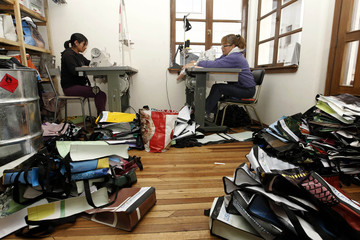 Tailors sew sailcloth into handbags and wallets, in the office of recycling company Fui Reciclado, in Quito