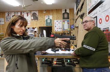 Ulrik Mitchell, (L) tries out a hand gun as her husband Bill, (R) looks on at the Ringmasters of Utah gun range and store,