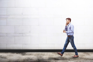 Young motivation Businessman talk via smart phone while walk outdoor building, Lifestyle of modern male use technology to communicate in business concept