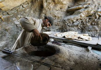 An afghan man puts bread into an oven in the kitchen of an Afghan National Police station near the city of Mara Wara in Afghanistan's Kunar Province