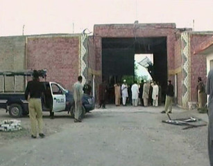 Police officers and people stand near a damaged jail gate after inmates escaped from the prison in the town of Bannu in this still image taken from video