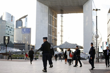 French policemen patrol in front of the Arche de la Defense at La Defense business district in Nanterre after a series of deadly attacks in Paris