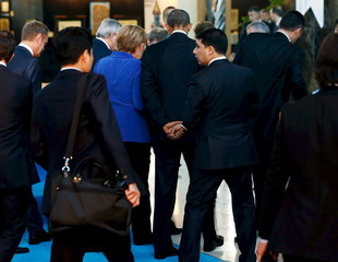 Obama departs with Merkel after participating in a family photo with fellow world leaders at the start of the G20 summit at the Regnum Carya Resort in Antalya, Turkey