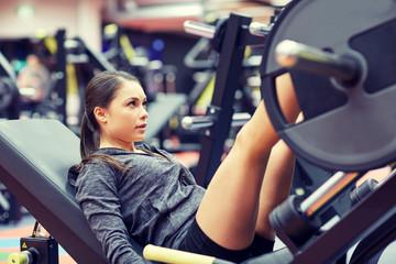 woman flexing muscles on leg press machine in gym