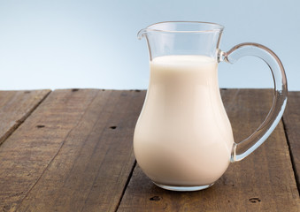 Fresh whole milk in glass jug on rough wooden table background