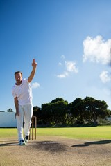 Full length of man bowling while standing on cricket field