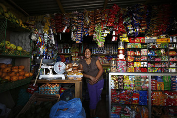 Irma Huaman poses for a photo in her grocery store in Gosen City, a slum in the Villa Maria del Triunfo municipality on the outskirts of Lima