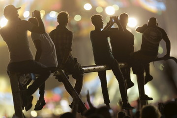 Fans take photographs while sitting on a bar during a free outdoor concert by the Rolling Stones at the Ciudad Deportiva de la Habana sports complex in Havana