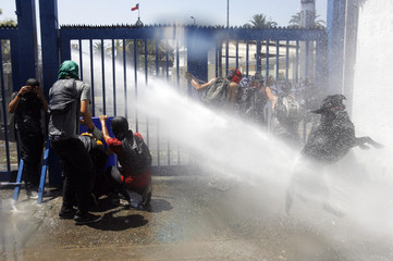 Riot police spay water on student protesters during a demonstration in Santiago