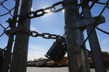 The gates of a school bus yard are locked after drivers walked off the job in the morning in Boston
