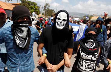 Masked students of the National Autonomous University of Honduras (UNAH) take part in a march protest against the new academic rules promoted by authorities of the UNAH, in Tegucigalpa
