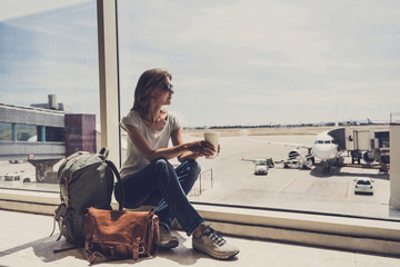 Young woman in the airport, looking through the window at planes and drinking coffee, travel, vacations and active lifestyle concept