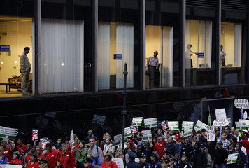 Workers from the Bank of India watch from a window as Occupy Wall Street protesters march 47th Street in New York