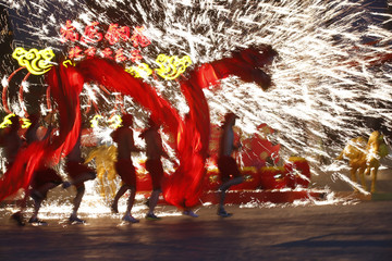 Dancers perform a fire dragon dance during a folk art performance to celebrate traditional Chinese Spring Festival