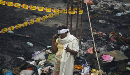 A eunuch speaks on a mobile phone at the site of Sunday's fire that broke out at a community center in New Delhi