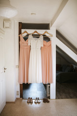 wedding dress hanging beside bridesmaids dresses