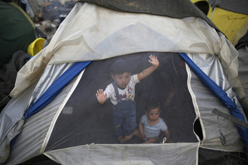 Children look out from a tent at a makeshift camp for migrants and refugees at the Greek-Macedonian border near the village of Idomeni