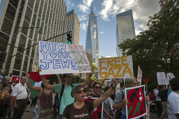 """One World Trade Center is seen in the background as activists hold placards while shouting """"Free, free Palestine"""" and """"Not another nickel, not another dime, no more money for Israel's crimes,"""" during a protest march through Lower Manhattan, New York"""
