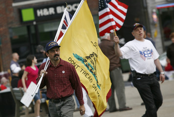 Men carry flags outside an H&R Block Tax preparation office during a tax day rally by Tea Party activists in the New York City suburb of New City