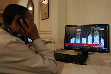 An Egyptian journalist in Sanaa watches the televised trial of Gamal and Alaa Mubarak in Cairo