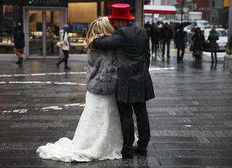 A couple embraces during light snowfall at Times Square in New York