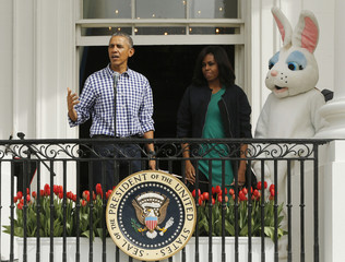 President Obama speaks to crowd as first lady and an actor dressed as the Easter Bunny look on during White House Easter Egg Roll at the White House in Washington