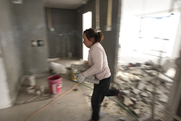 Deng Qiyan carries debris as she works at a home renovation site in Beijing