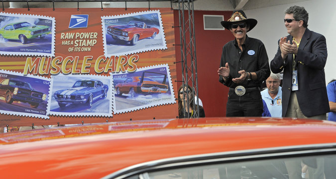 U.S. Postmaster General Donahoe reacts after racing legend Petty unveiled the new Muscle Cars Forever stamps at a dedication ceremony at the Daytona International Speedway