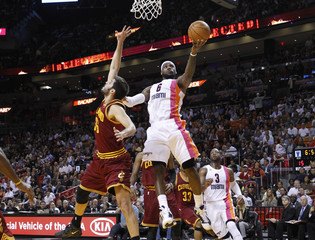 Miami Heat LeBron James gets past Cleveland Cavaliers Omri Casspi to score during their NBA basketball game in Miami
