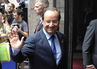 France's President Hollande waves as he arrives at a European Union leaders summit in Brussels