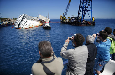 People take pictures of the capsized cruise liner Costa Concordia lying surrounded by cranes outside Giglio harbour