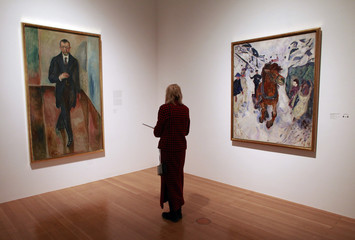 """A visitor looks at the paintings """"Thorvald Lochen"""" (L), 1917 and """" Galloping horse"""", 1910 by Norwegian artist Edvard Munch presented at an exhibition in Frankfurt"""