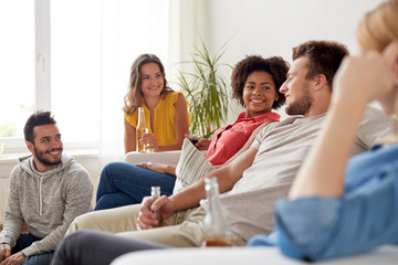 group of happy friends with drinks talking at home