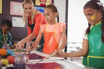 Teacher assisting schoolkids in drawing class