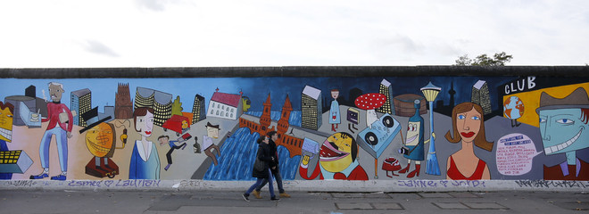 """People take pictures of newly painted artwork of contemporary German pop artist Avignon at the open air """"East Side Gallery"""" in Berlin"""