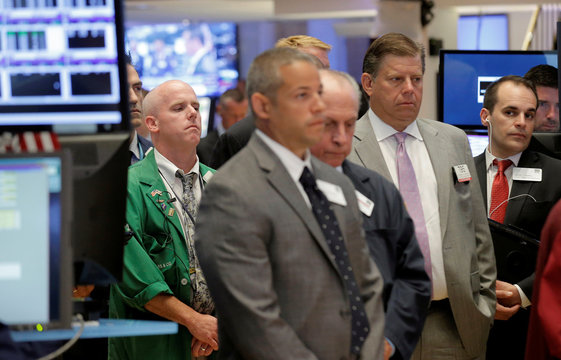 Traders pause for a moment of silence before the opening bell, for the fallen police officers in Baton Rouge, on the floor of the NYSE