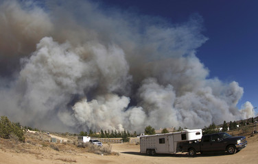 People evacuate their horses as smoke fills the skies in this photo taken with an extreme wide angle lens at the so-called Bluecut Fire in San Bernardino County, California