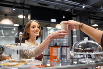 happy woman taking coffee cup from seller at cafe