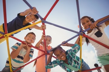 Portrait of happy schoolkids looking through dome climber