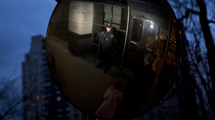A policeman is reflected in a parabolic mirror outside the South Park Tower rental apartment in Manhattan, New York