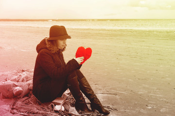 A young woman in a hat and coat sits on the shore of the bay on a fishing net with a plush heart in her hands, Bright toning, copy spase