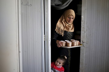 Syrian refugee Burooq Al Zubi carries juice in the kitchen of the family accommodation at Al Zaatari refugee camp in the Jordanian city of Mafraq, near the border with Syria