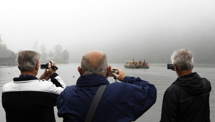 Tourists take pictures of boat loaded with cows at Lake Koenigssee