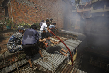 A man tries to move a water hose towards the burning houses while others hold him as they try to put out the fire in Kathmandu